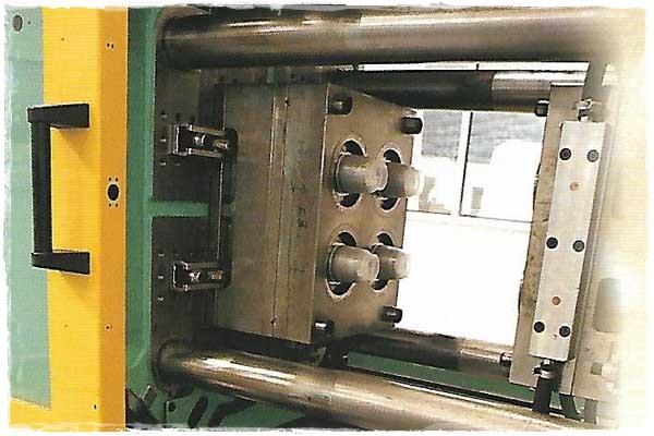 Detalle de los moldes de vasos en la máquina de inyección